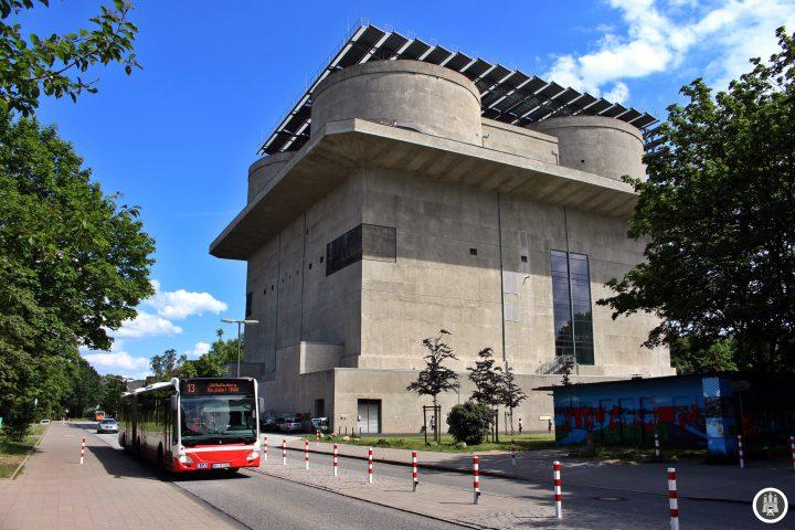 Hier an der Veringstraße steht ein Hochbunker, der im Zuge der Internationalen Bauausstellung in ein zukunftsweisendes Energiekraftwerk umgebaut wurde. Der Bunker bündelt und erzeugt Energie für 800 Wohneinheiten im umliegenden Viertel. Darüber hinaus wurde in den Bunker ein Café mit Glasfront integriert.